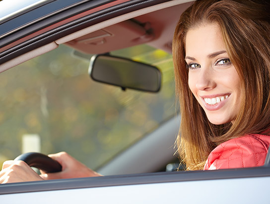 Car Insurance for Matthews, NC, with Woman Smiling in her Insured Auto